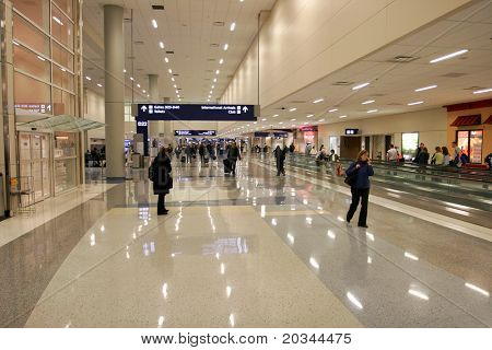 Passengers in modern airport (recognizable faces are blurred)