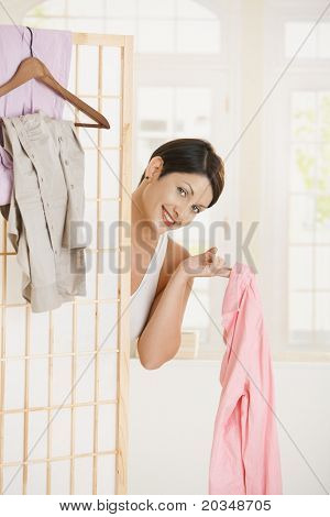 Sexy young woman undressing, looking out beckoning behind dressing panel, showing up pink shirt.?