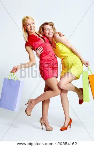 Dois compradores bonitos com paperbags se divertindo sobre fundo branco