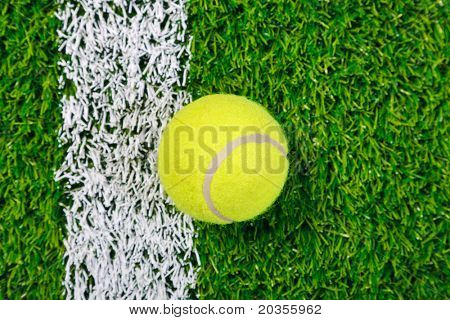 Photo of a tennis ball on a grass next to the white line, shot from above.