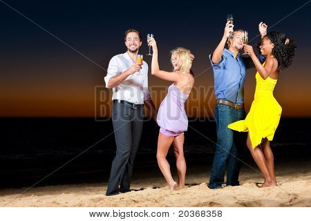 People (two couples) on the beach having a party and lots of fun in the sunset, they are wearing smart casual clothes and dance