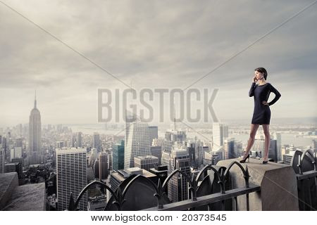 Beautiful businesswoman standing on the rooftop of a skyscraper over a city