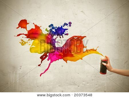 Man's hand spraying colored paint