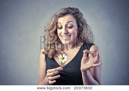 Smiling beautiful woman wavering a daisy