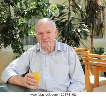 portrait of old man with orange juice