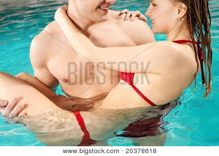 Handsome guy holding his girlfriend and looking at her in swimming pool