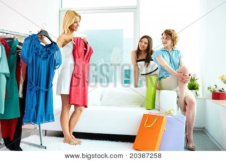 Image of pretty females looking at their friend trying on smart dress while choosing a right one