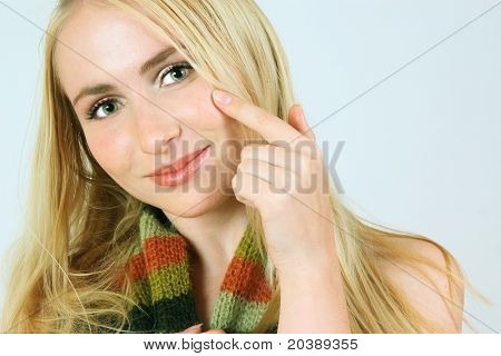 Young girl with green eyes and long blond hair playfully pointing at her cheek