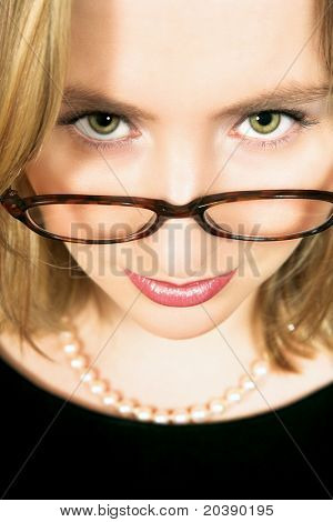 Young blond woman face close-up wearing strict frame glasses and pearls