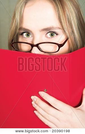 Young stressed blond business woman with large green eyes in glasses hiding behind a red folder