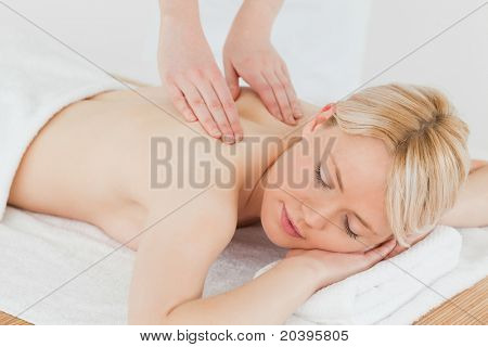 Closeup of young gorgeous blonde woman receiving a back massage in a spa center