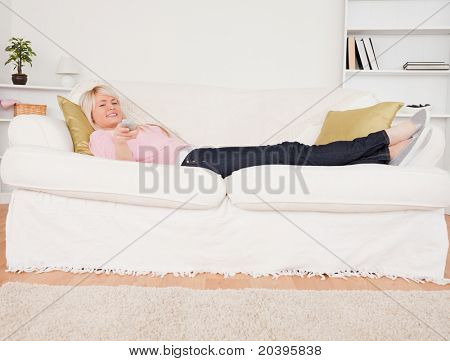 Pretty blonde female watching tv while lying on a sofa in the living room
