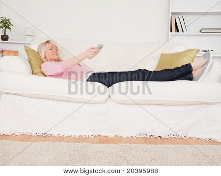 Pretty blonde woman watching tv while lying on a sofa in the living room