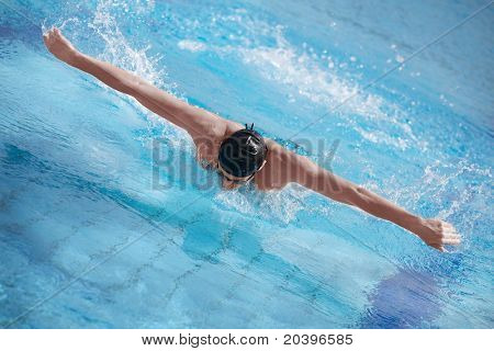 aerial view of swimmer in cap breathing performing the butterfly stroke