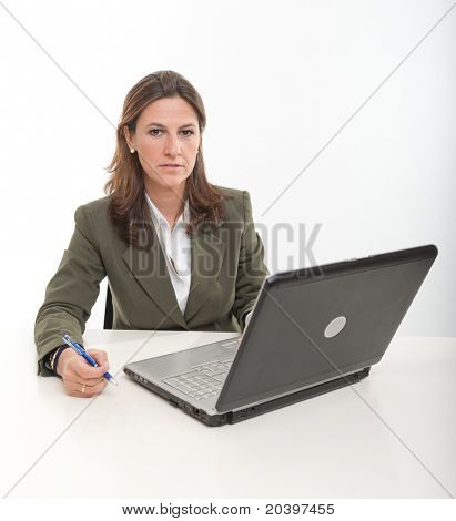 Serious business woman sitting in front of a laptop