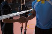 Male volleyball players shaking hands through net at court poster