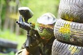 picture of paintball  - paintball sport player wearing protective mask aiming gun from shelter under gunfire attack with paint splash - JPG