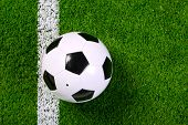 Photo of a leather football or soccer ball on a grass next to the white line, shot from above.