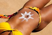 pic of sun tan lotion  - Woman with suncream on the belly at the beach in summer - JPG