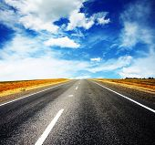 Asphalt road and bright blue sky with fluffy clouds poster