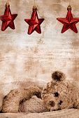 stock photo of teddy-bear  - teddy bear in blanket under three Christmas red stars on grunge background with copy space  - JPG