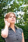 Relying on hand-ear listening young woman poster