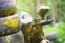 pic of paintball  - paintball sport player wearing protective mask aiming gun from shelter under gunfire attack with paint splash - JPG