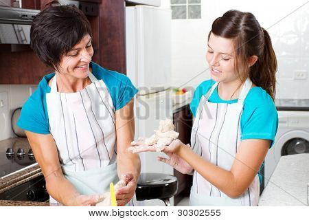 happy mother and teenage daughter baking in kitchen