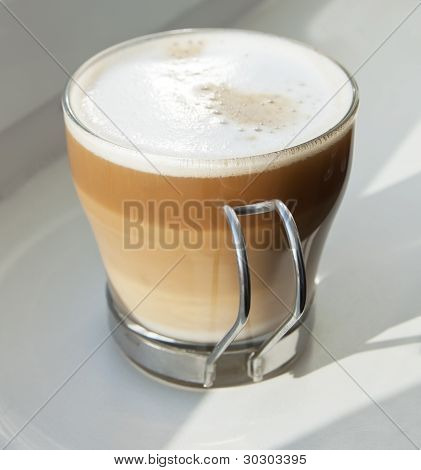 Cappuccino in a glass cup over white
