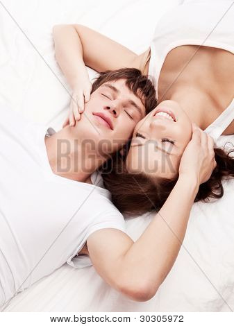 happy young beautiful couple in bed at home, top view