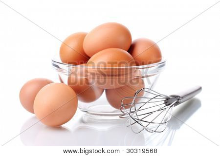 Metal whisk for whipping eggs and brown eggs in bowl isolated on white