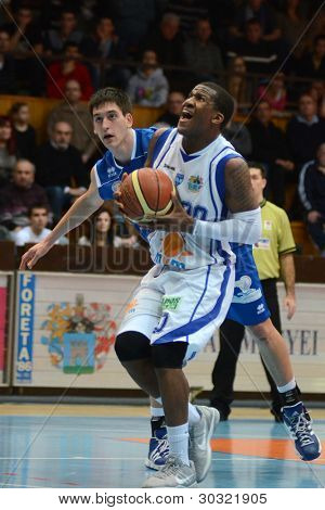 KAPOSVAR, HUNGARY – FEBRUARY 18: Kwadzo Ahelgebe (in white) in action at a Hungarian Championship basketball game with Kaposvar (white) vs. Fehervar (blue) on February 18, 2012 in Kaposvar, Hungary.