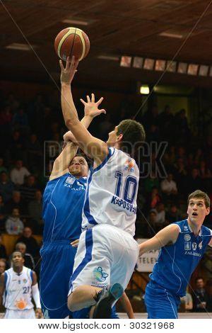 KAPOSVAR, HUNGARY – FEBRUARY 18: Gergely Kutasi (white 10) in action at a Hungarian Championship basketball game with Kaposvar (white) vs. Fehervar (blue) on February 18, 2012 in Kaposvar, Hungary.