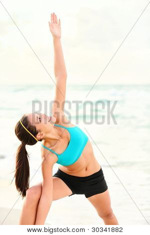Yoga stretching woman on beach. Serene sporty woman doing yoga poses during outdoor. Beautiful happy smiling mixed race Chinese Asian / Caucasian female fitness model outside.