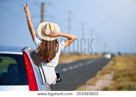 poster of Slim Pretty Woman In Straw Hat Enjoying Road Trip On A Summer Day. Excited Young Female Raising Her