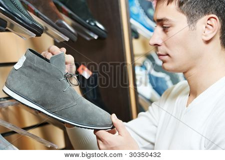 Young man choosing shoes during footwear shopping at shoe shop