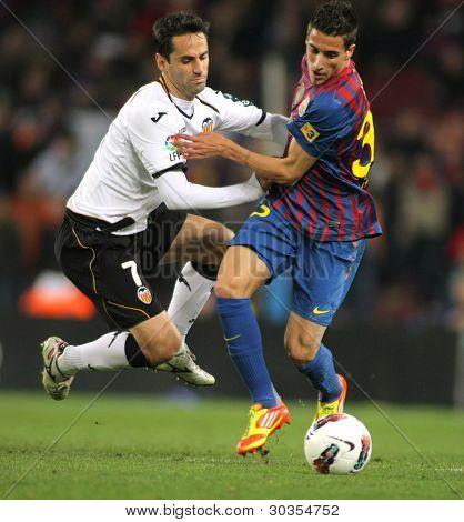 BARCELONA - FEB 19: Jonas Gonasalves of Valencia CF vies with Cristian Tello of FC Barcelona during the Spanish league match at the Camp Nou stadium on February 19, 2012 in Barcelona, Spain