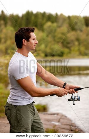 A man fishing on a inerior lake with forest in the background