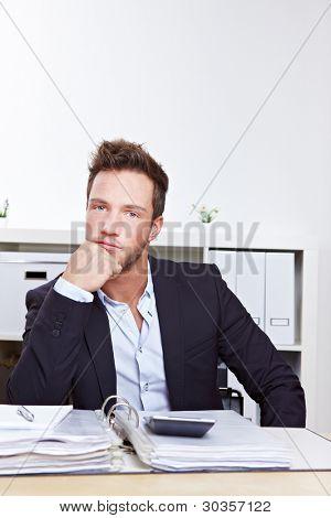 Homem de negócios pensativo com arquivos sentado no escritório de turismo