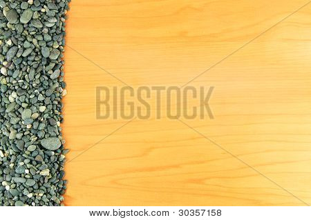 pile of stones on beside on the wood texture background