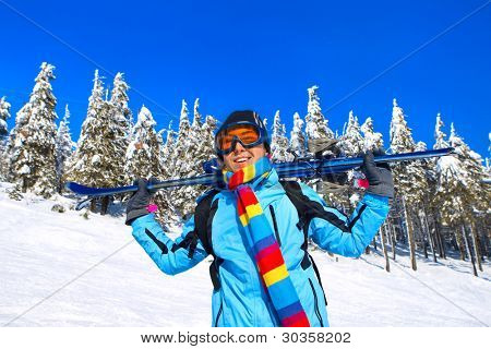 Young male skier holding ski; blue jacket; black pant; horizontal orientation