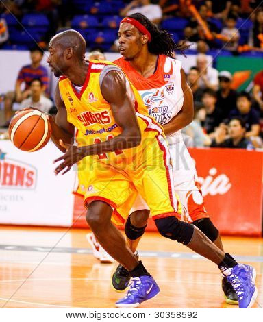 KUALA LUMPUR - FEBRUARY 19: Singapore Slingers' Louis Graham (yellow) dribbles past Tiras Wade at the ASEAN Basketball League match on February 19, 2012 in Kuala Lumpur, Malaysia. Dragons won 86-71.