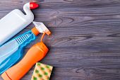 House Cleaning Supplies On Wooden Background. Set Of Plastic Bottles With Cleaning Liquid And Kitche poster