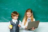 Classroom. First School Day. Teacher Schoolgirl Helping Kids With Their Homework In Classroom At Sch poster