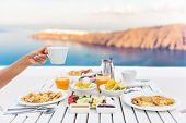 Breakfast woman drinking coffee at luxury hotel resort restaurant table Mediterranean sea view in Sa poster