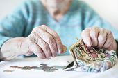 Detailed Closeup Photo Of Unrecognizable Elderly Womans Hands Counting Remaining Coins From Pension  poster