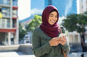 Pretty muslim woman using mobile phone outdoor. Arabic woman wearing hijab using smartphone on the s poster