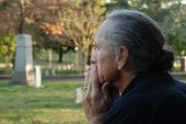 image of burial  - Man sitting at gravesite with a look of sadness - JPG
