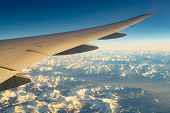 Wing Of Plane Over Mountain Cover With White Snow. Airplane Flying On Blue Sky. Scenic View From Air poster