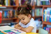Little Girl Indoors In Front Of Books. Cute Young Toddler Sitting On A Chair Near Table And Reading  poster